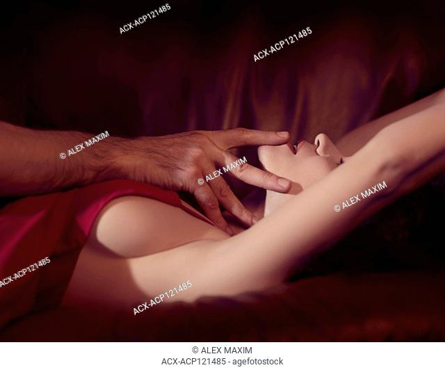 Artistic sensual couple, beautiful woman in red dress, closeup of a face, man hands touching her lips