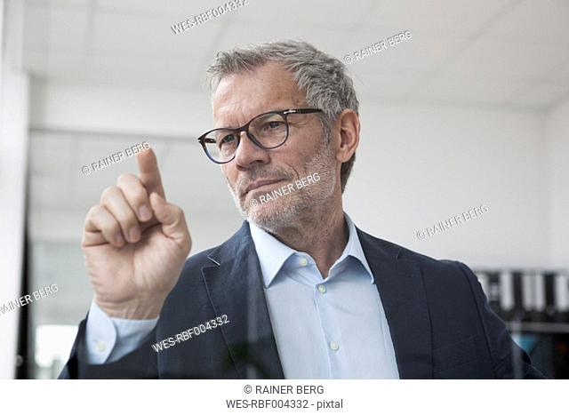 Successful businessman in office touching glass screen