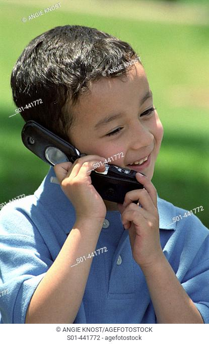 Hispanic boy, aged 5 - 6, talking on cell phone outdoors, smiling