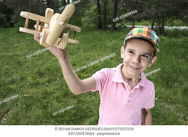 Child play with a wooden plane in the mountain. Forest