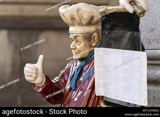 Chef at the door of a restaurant showing the menu, MADRID, SPAIN, EUROPE