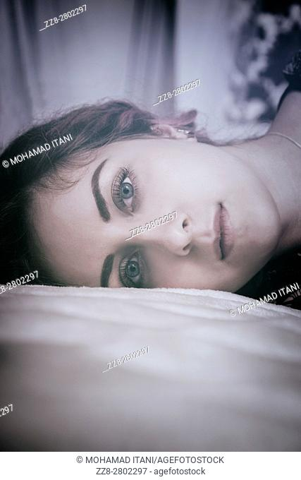 Sad woman laying down in bed staring