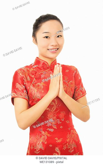 Beautiful Chinese woman wearing a traditional dress known as a Chipao isolated on a white background