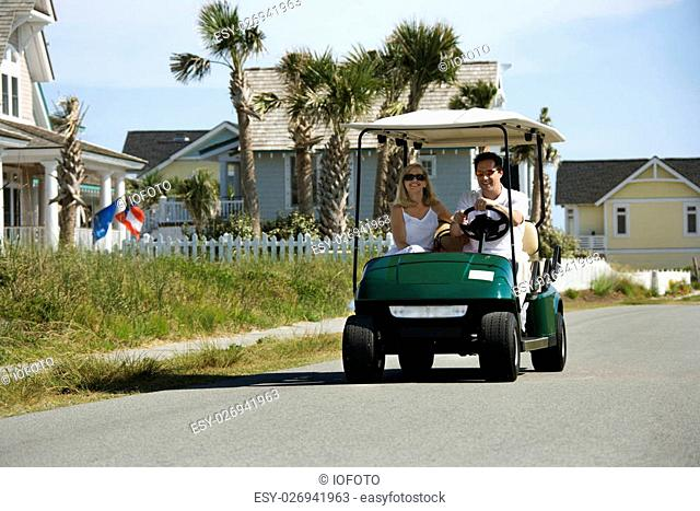 Caucasian mid-adult man and woman driving golf cart down residential street