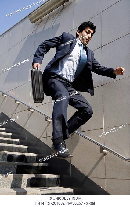 Businessman rushing down stairs of a subway, Gurgaon, Haryana, India