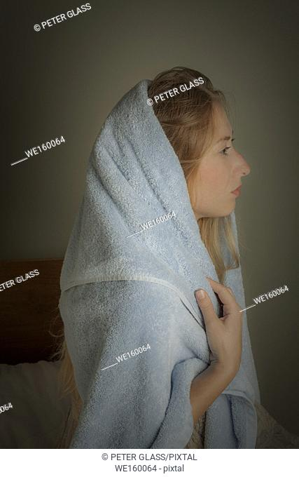 Profile of a young woman with a towel wrapped around her head and shoulders