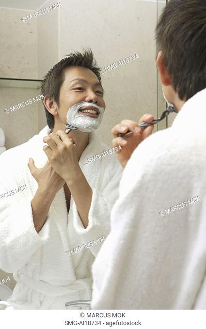 Man in robe, shaving face