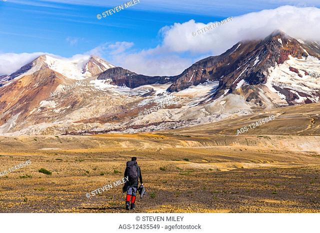 A backpacker crosses the exotic landscape of the ash and pumice-covered Valley of Ten Thousand Smokes in Katmai National Park, with Mt