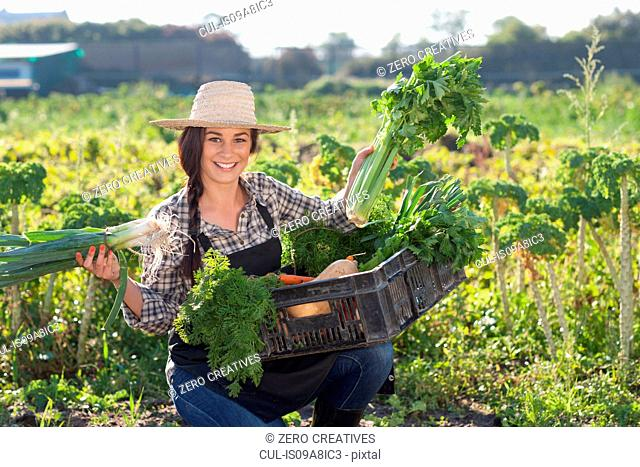 Young woman with vegetables grown at farm