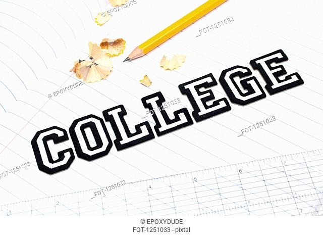 Varsity font stickers spelling out College atop a lined paper notebook with ruler and pencil