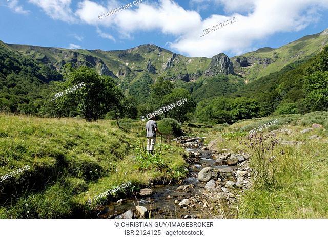 Hiker in Chaudefour Valley natural reserve, Parc Naturel Regional des Volcans d'Auvergne, Auvergne Volcanoes Regional Nature Park, Puy de Dome, France, Europe