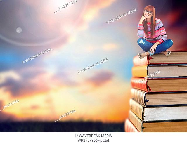 Woman sitting on Books stacked by sunset sky