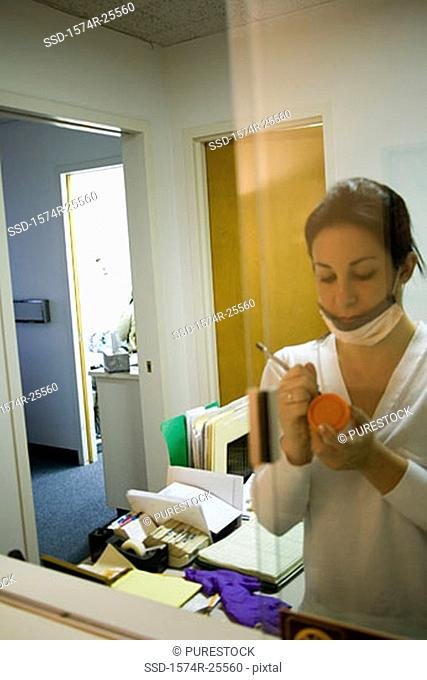 Female nurse writing on a urine sample bottle