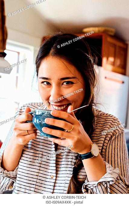 Woman holding tea cup to mouth looking at camera smiling
