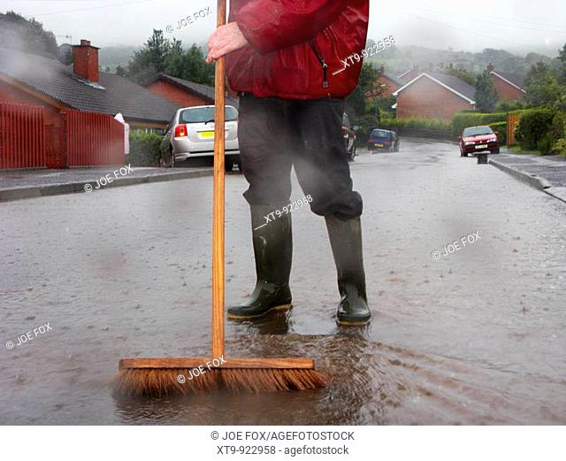 man with large brush wearing wellington boots clears away flood water from rain and river overflow flooding a street in newtownabbey, county antrim, uk