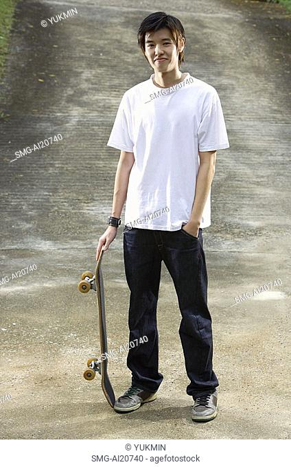 Young man with skateboard, hand in pocket