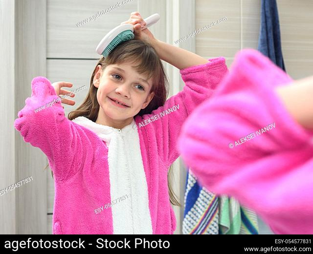 Girl combing her hair in the bathroom early in the morning