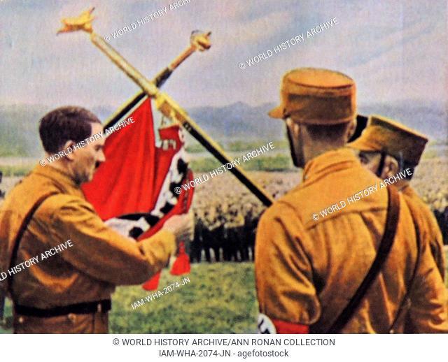 Adolf Hitler holds a Nazi Flg at a youth rally. Circa 1933