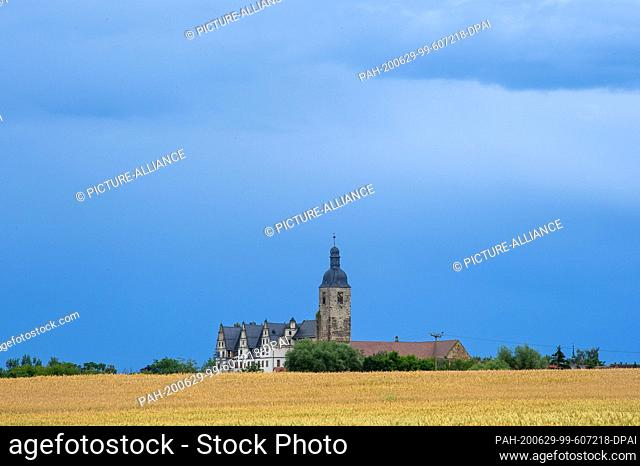 29 June 2020, Saxony-Anhalt, Zeppernick: Rain clouds pass over a cornfield, behind which the Leitzkau castle can be seen