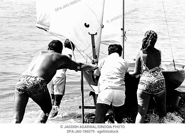Man and woman pushing boat Madh Island Mumbai Maharashtra India Asia 1973