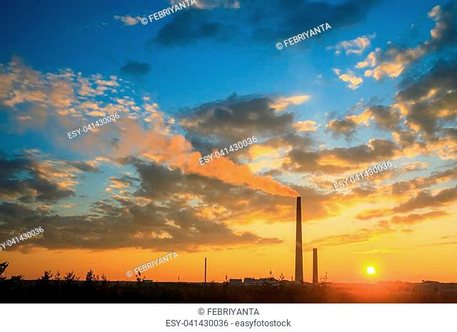 View of a smelter stack of a nickel plant showing the emission on the air with sunset sky as as background