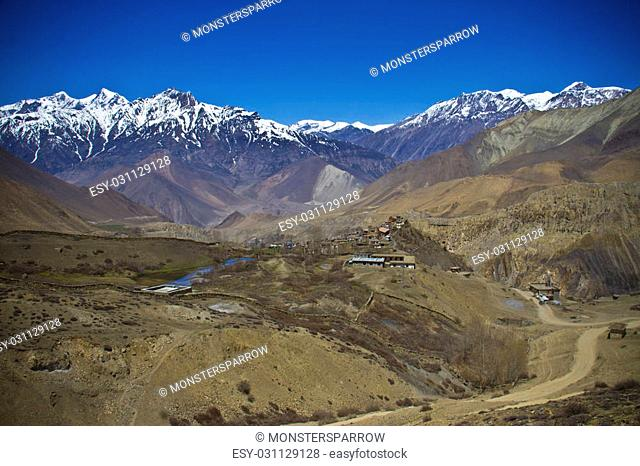 Village in the valley surrounded snowy Himalayan peaks