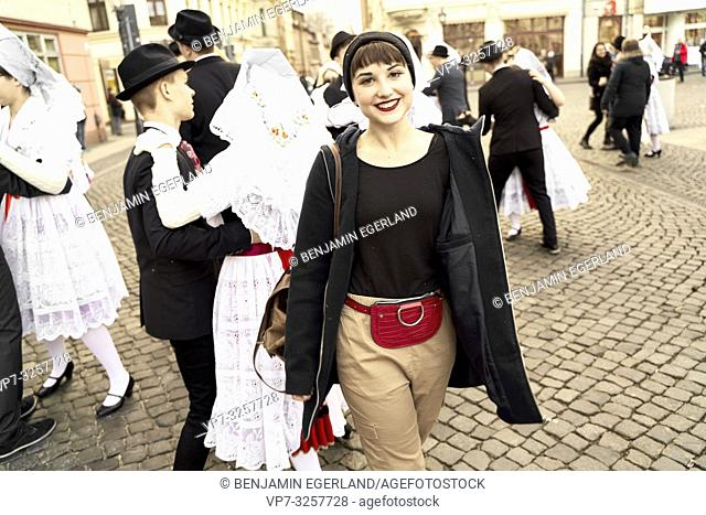 woman in leisure clothes at German tradition celebration in front of dancing people wearing traditional costume, outdoors at street, in city Cottbus