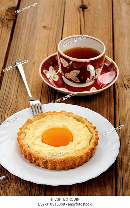 Peach tarts and cups of black tea on wooden background