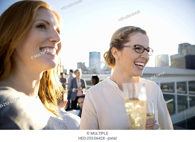 Smiling businesswomen drinking champagne on urban rooftop