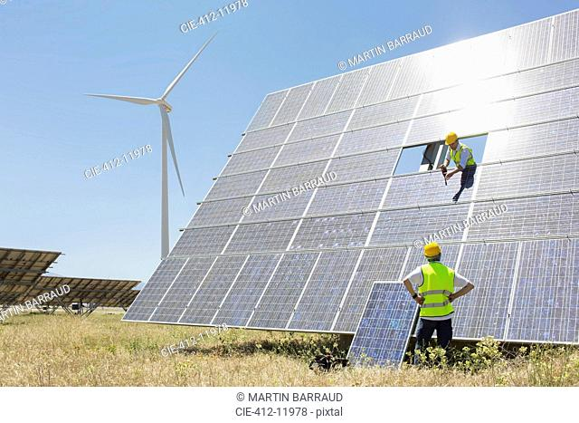 Workers examining solar panel in rural landscape