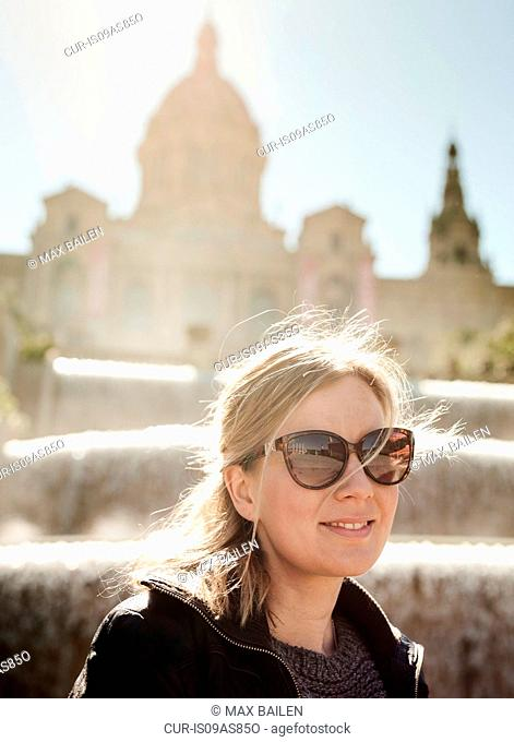 Portrait of mid adult woman wearing sunglasses in front of Catalonia Museum of Art, Barcelona, Spain