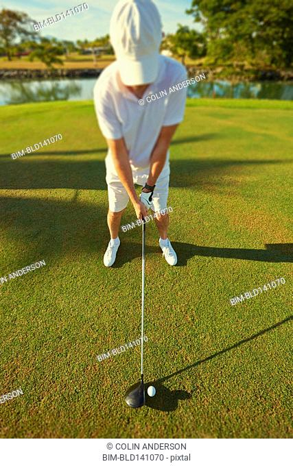High angle view of Caucasian golfer holding club at ball