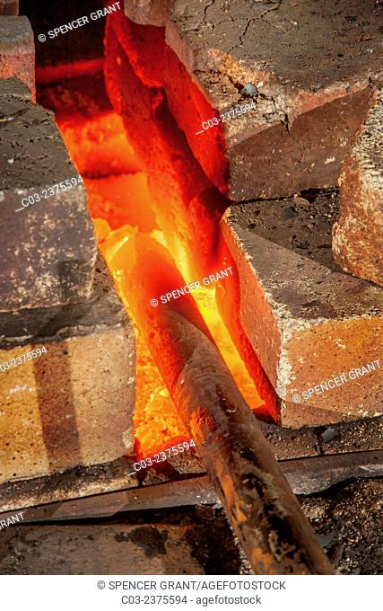 An iron bar is heated red-hot in the forge of a blacksmith's shop. Note fire bricks