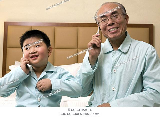 Middle-aged man and grandson talking on cell phones in pajamas