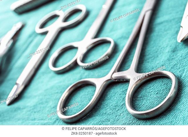 Some scissors for surgery on a tray in an operating theater, conceptual image, horizontal composition