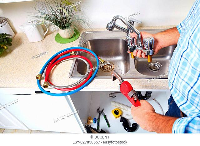 Plumber on the kitchen. Renovation and plumbing