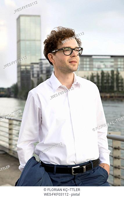Germany, Berlin, portrait of businessman relaxing at River Spree