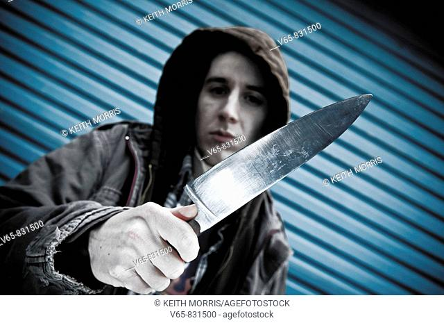 young man with a knife, wearing hoodie, looking aggressive and threatening at the camera