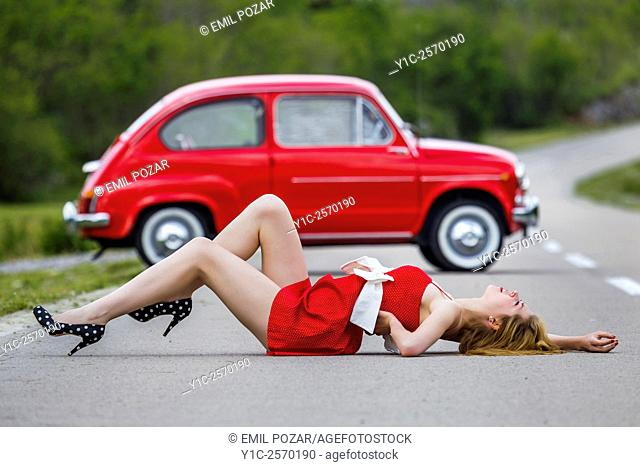 Teen girl spread before Red classic car