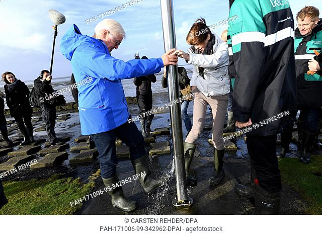 German federal president Frank-Walter Steinmeier and his wife Elke Buedenbender can be seen cleaning their boots from mud near Hamburger Hallig, Germany