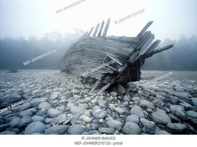 Broken boat on pebbles underwater