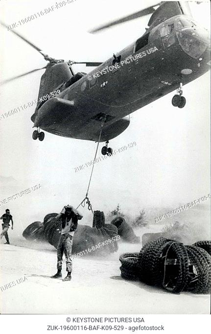 1958 - Vietnam war, barbed wire by air; A powerful Ch-46A helicopter churns up dust as it hovers to haul up coils of barbwire at Chu Lai to carry to Korean...