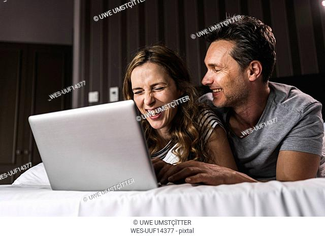 Happy couple lying on bed at home having fun with laptop