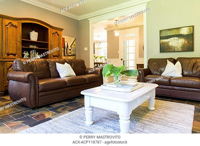 White wooden coffee table with brown leather sofas and wooden buffet in the living room with earth tone slate flooring inside a contemporary cottage style home