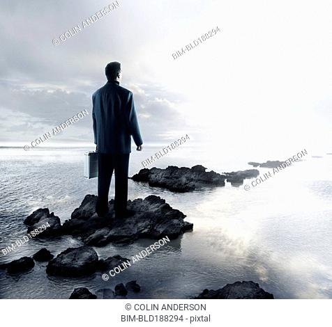 Portuguese businessman standing on rocks in water