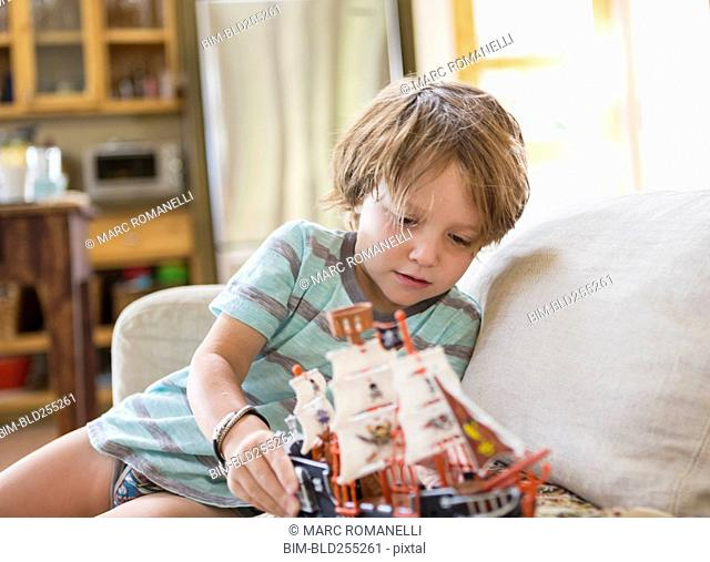 Caucasian boy sitting on sofa playing with toy boat