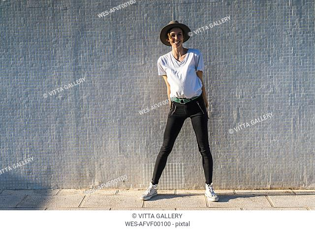 Laughing woman wearing hat standing in front of tiled wall at sunlight