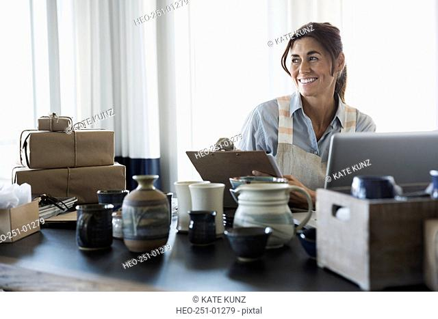 Smiling woman with pottery and clipboard