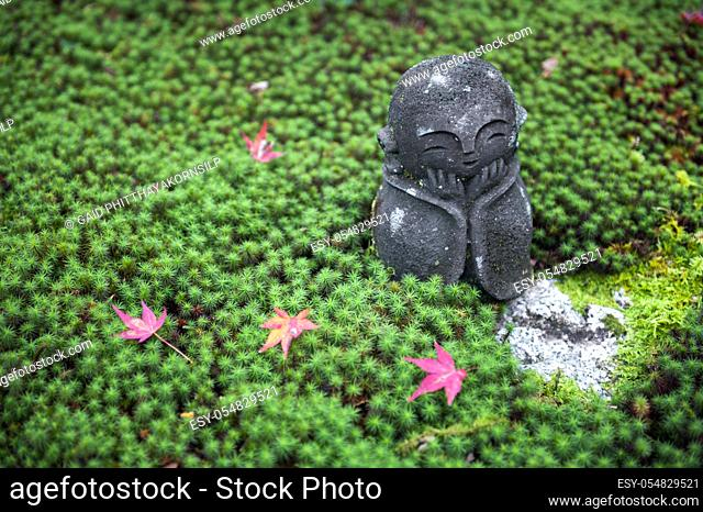 Stone statue of Jizo on ground covered by green star moss and red maple leaves during autumn in a garden at Enkoji temple in Kyoto, Japan