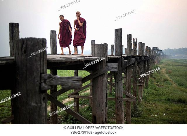 Two Buddhist monks walk along the U Bein bridge at sunrise, Amarapura, Myanmar